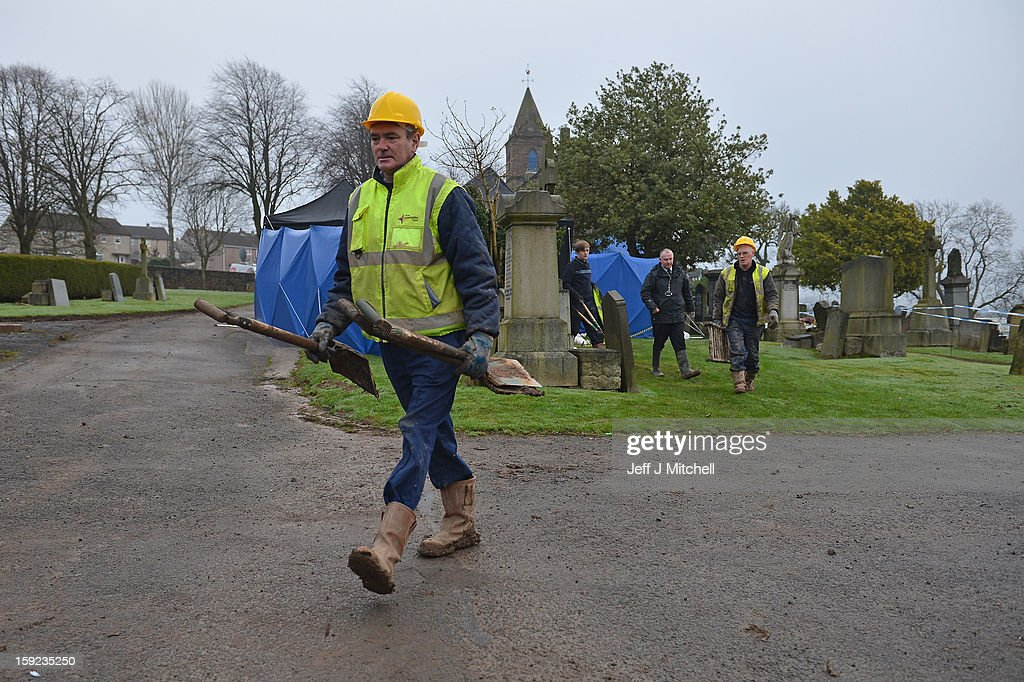 Workmen takeaway their tools following the conformation that a grave at Old Monkton cemetery does not contain the body of missing schoolgirl Mora Anderson on January 10, 2013 in Coatbridge, Scotland. Forensic specialists have spent the past three days exhuming the family burial plot of Sinclair Upton, an acquaintance of Alexander Gartshore, a former bus driver and convicted rapist linked to the disappearance of Moira. The 11-year-old school girl went missing in 1957.