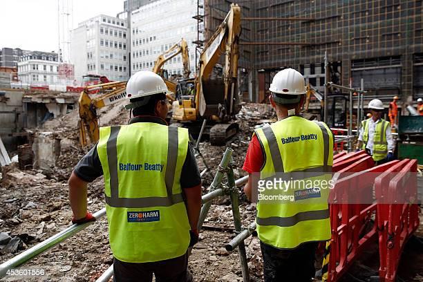 Workmen watch as excavators collect rubble during building works at Balfour Beatty Plc's St James's Market construction site a joint Crown Estate and...