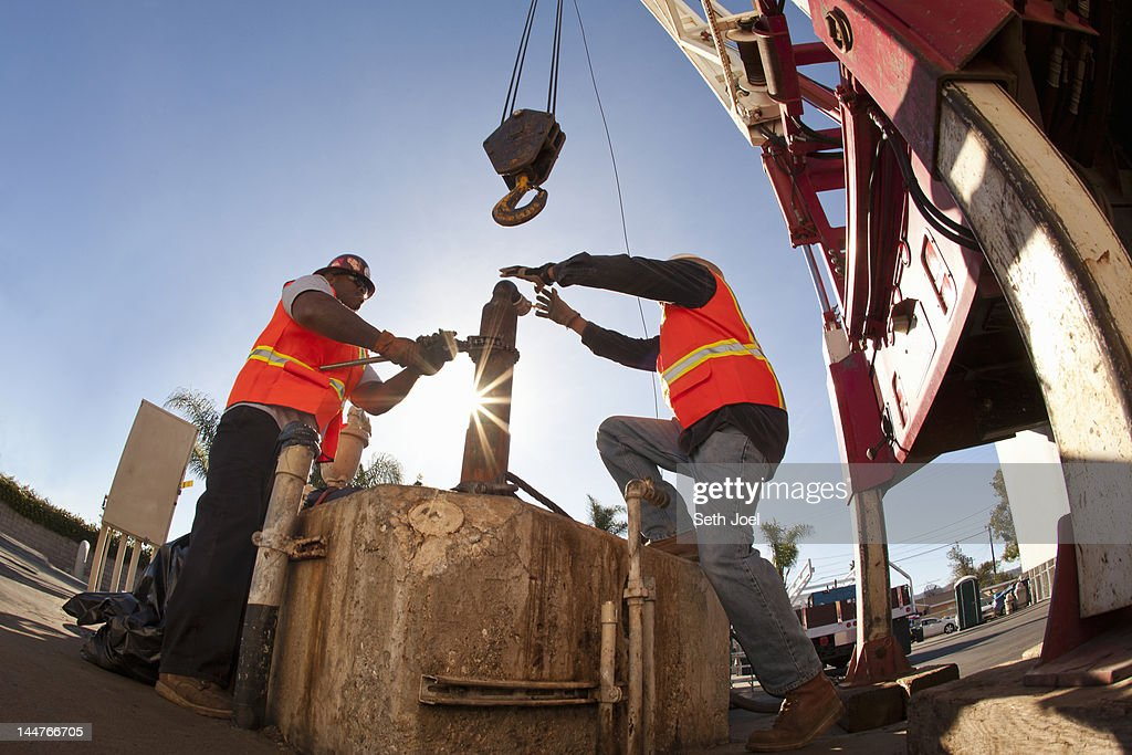 Workmen working with crane to install piping : Stock Photo