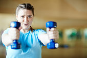 Young female in blue t-shirt doing effective exercise with dumbbells while working out in gym