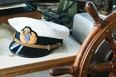 Workplace of the captain. Still-life on marine subject matter with a peak-cap and a steering wheel