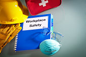 """Workplace safety handbook manual and equipment. A red first aid kit in the back with a white cross on it, a hard hat on top of a pair of work gloves, a manual with the words """"Workplace Safety"""" written"""