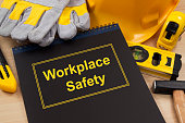 Workplace safety manual with construction and safety equipment on wooden table.