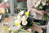 Workshop florist, making bouquets and flower arrangements. Woman collecting a bouquet of flowers. Soft focus .