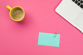 Coffee, laptop and adhesive note on pink background