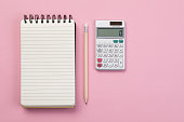 Spiral notebook, pencil and calculator on pink background
