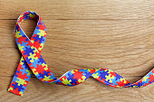 World Autism awareness and pride day with Puzzle pattern ribbon on wooden background