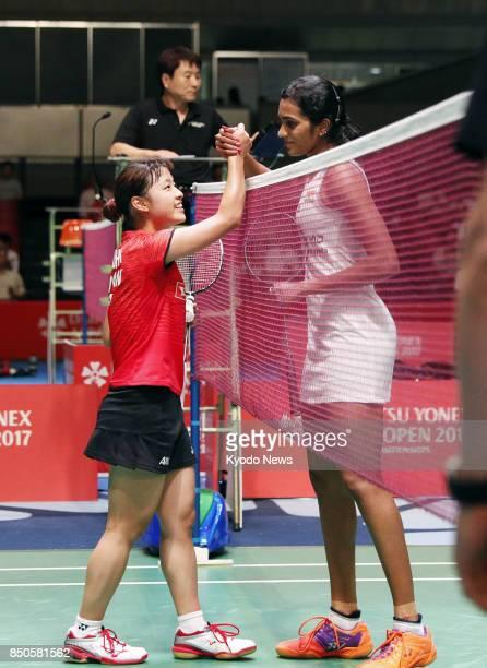 World badminton champion Nozomi Okuhara of Japan and her world championships final opponent Pusarla Sindhu of India shake hands after Okuhara beat...