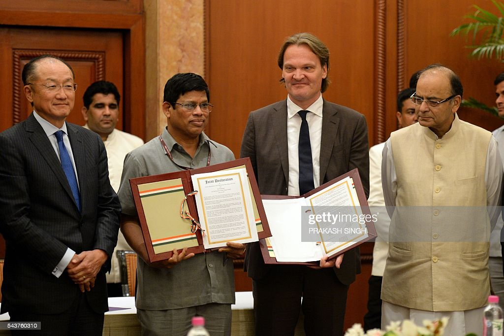 World Bank Group President, Jim Yong Kim (L) and Indian Finance Minister, Arun Jaitley (R) pose with Indian Ministry of New and Renewable Energy Secretary, Upendra Tripathy (2L) and World Bank Country Director, Unno Ruhl (2R) following the signing and exchange of agreement in New Delhi on June 30, 2016. The World Bank Group June 30, signed an agreement with the International Solar Alliance (ISA) to collaborate on increasing solar energy use around the world, with the goal of mobilizing one trillion dollars in investments by 2030. / AFP / PRAKASH