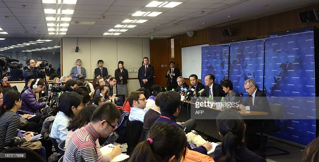 World Bank Group President Jim Yong Kim (3rd R, seated at table at R) attends a press conference in Beijing on November 30, 2012. The World Bank is to launch a joint study with Beijing on urbanisation in China, one of the great human migrations of modern times, it said on November 30.