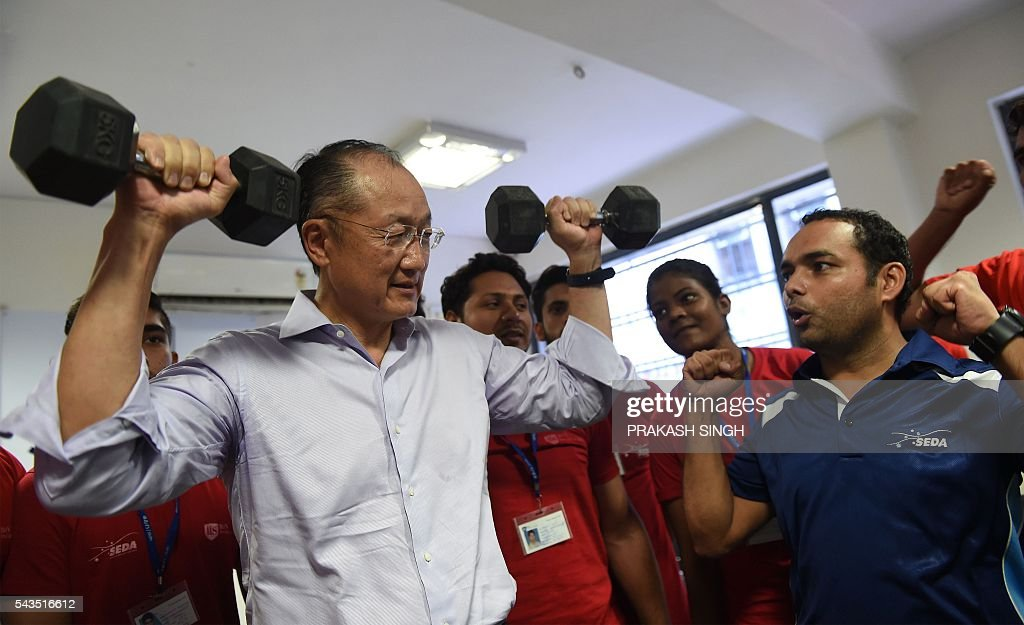 World Bank Group President Jim Yong Kim (L) lifts weights during a visit to a vocational skills development centre in New Delhi on June 29, 2016. / AFP / Prakash SINGH