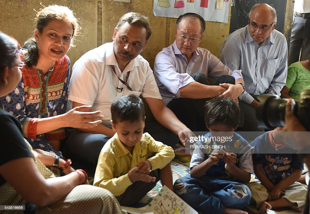 World Bank Group President Jim Yong Kim (2R, top) listens to an official talk at the Integrated Child Development Services (ICDS) Centre in New Delhi on June 29, 2016. / AFP / Prakash SINGH