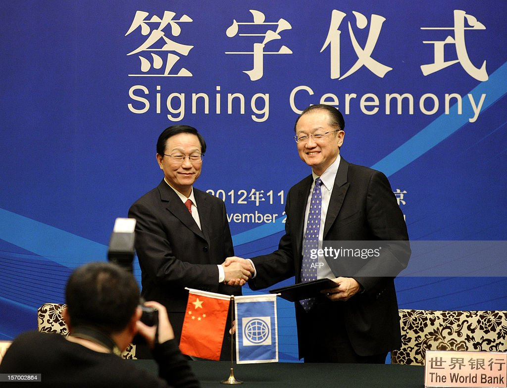 World Bank Group President Jim Yong Kim (R) shakes hands with Chinese Finance Minister Xie Xuren (L) during a signing ceremony in Beijing on November 27, 2012. Jim Yong Kim started his first visit to China as Worldbank president on November 27 by signing an agreement with the Chinese government to launch a new knowledge platform to improve urban transport, focusing on low-carbon emissions, as China's fast growing cities are among the most polluted in the world.