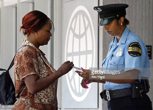 World Bank security guard checks a woman's photo ID before letting her to enter the World Bank headquarters August 2 2004 in Washington DC The...