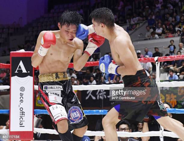 World Boxing Association super bantamweight champion Shun Kubo of Japan receives a punch from US challenger Daniel Roman during their title bout in...