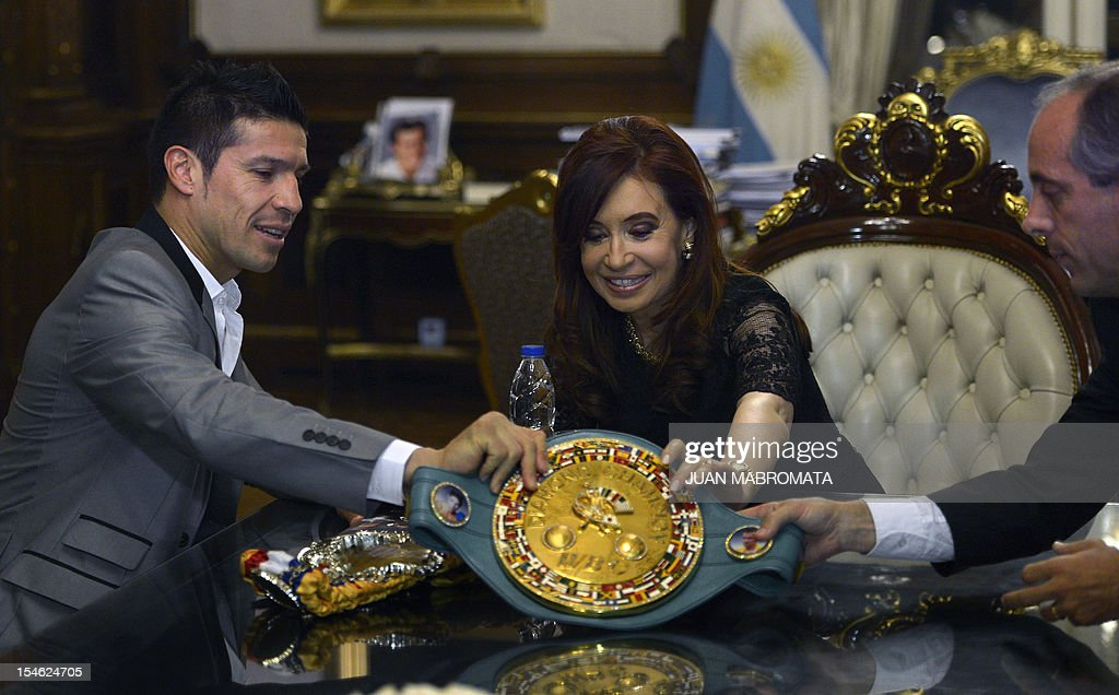 World Boxing Council (WBC) middleweight champion boxer, Argentine Sergio Martinez (L), Argentine President Cristina Fernandez de Kirchner (C) and Argentine Sports Secretary, Osvaldo Morresi, hold the WBC middleweight champion belt at the Government Palace in Buenos Aires on October 23, 2012. AFP PHOTO / Juan Mabromata