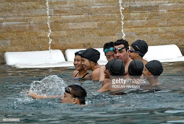World Champion Christian Sprenger of Australia gives a swimming clinic session to children with special needs on the rooftop pool of the Marina Bay...