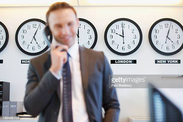 Relógios do mundo de Negócios no escritório atrás