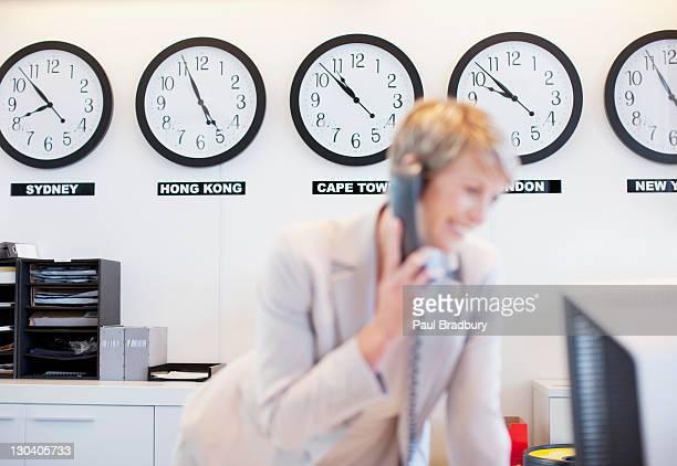 Horloges du monde derrière Femme d'affaires dans le bureau