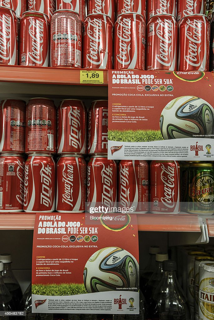 A World Cup advertisement is displayed next to cans of Coca-Cola Co. soda in a grocery store in Sao Paulo, Brazil, on Saturday, June 7, 2014. Companies like Coca-Cola Co. have spent millions on sponsorship of the FIFA World Cup in Brazil in hopes of burnishing their brand. Growing street violence promises to interrupt the multinational marketing bonanza as the games start on June 12. Photographer: Paulo Fridman/Bloomberg via Getty Images
