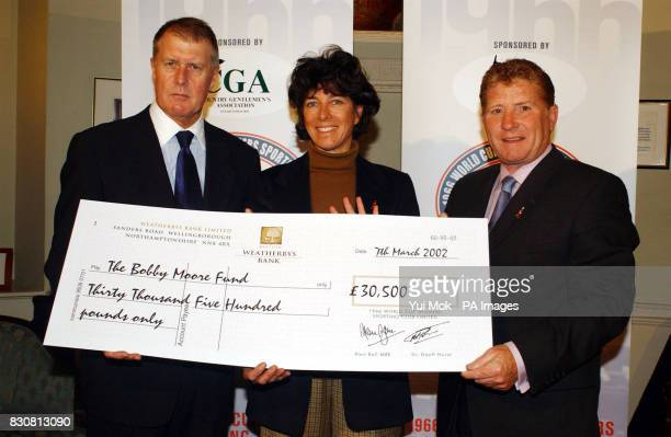 World Cup heroes Sir Geoff Hurst MBE and Alan Ball MBE present Stephanie Moore MBE with a cheque for 30500 for the Bobby Moore Fund for Cancer...
