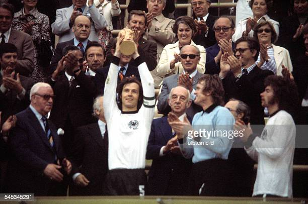 1974 FIFA World Cup in Germany Final in Munich Germany 2 1 Netherlands Captain Franz Beckenbauer raising the trophy at the award ceremony| right Sepp...