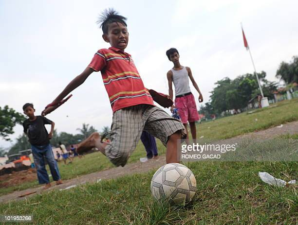 World Cup inspired Indonesian youths play football barefoot in Subang town in West Java on June 10 2010 World cup fever has swept in the muslim...
