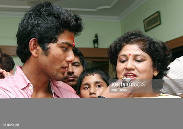 World Cupwinning India under19 cricket team captain Unmukt Chand offers his mother a piece of cake at his residence in New Delhi on Thursday 30th...