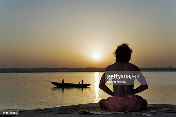 World famous yogi teacher Dr. Rakesh Yogi in pranamasana. A praying yoga posture. Sunrise over the Ganges River, India. (MR)