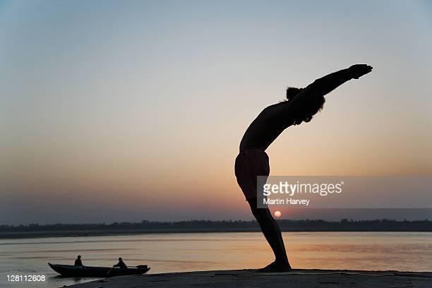 World famous yogi teacher Dr. Rakesh Yogi in the hasta utthan asana; raised arm yoga posture. Dancing yoga posture. Sunrise over the Ganges River, India. (MR)