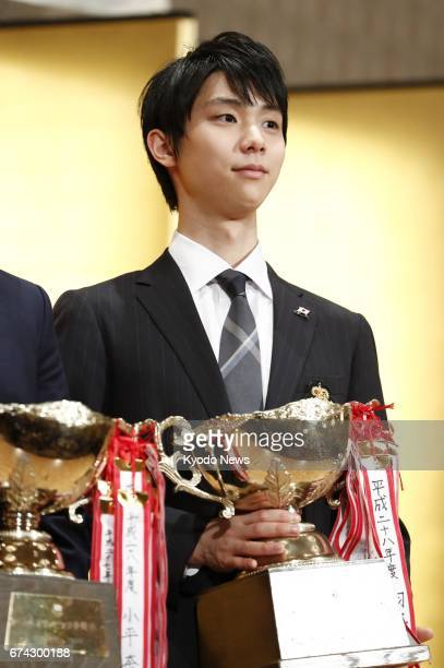 World figure skating champion Yuzuru Hanyu poses for photos at the Japan Skating Federation's annual awards ceremony in Tokyo on April 27 after being...