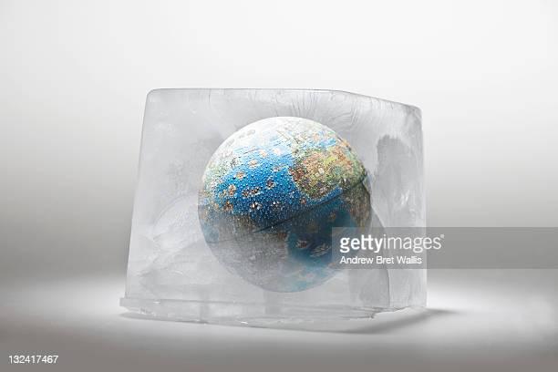 World globe frozen inside a block of ice