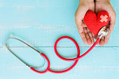 World health day, Healthcare and medical concept. Woman hand holding red heart with Stethoscope, notepad or notebook, thermometer and yellow Pill on Pastel white and blue wooden table background textu