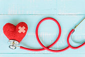 World health day, Healthcare and medical concept. Red heart with Stethoscope, notepad or notebook, thermometer and yellow Pill on Pastel white and blue wooden table background texture.
