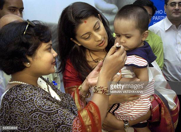 World Health Organisation and Oral Rehydration Salts Goodwill Ambassador Smriti Irani holds a child being fed an ORS solution at a function to mark...