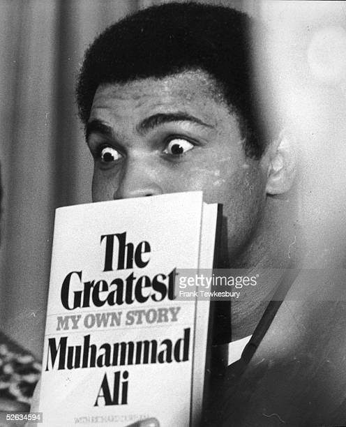 World heavyweight boxing champion Muhammad Ali during a press conference at the Savoy Hotel in London 9th March 1976 He is holding a copy of his...