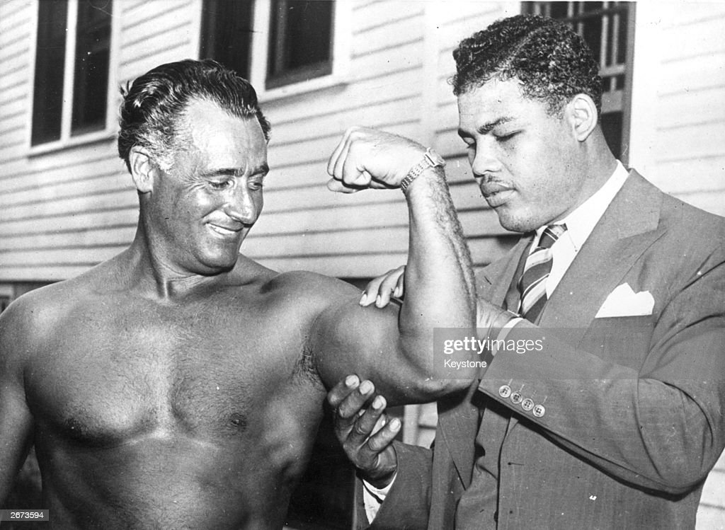 World heavyweight champion Joe Louis (1914 - 1981) admires the flexed bicep of Charles Atlas, considered by some to be the world's most perfectly developed man, at Madame Bey's Camp in Summit, New Jersey.