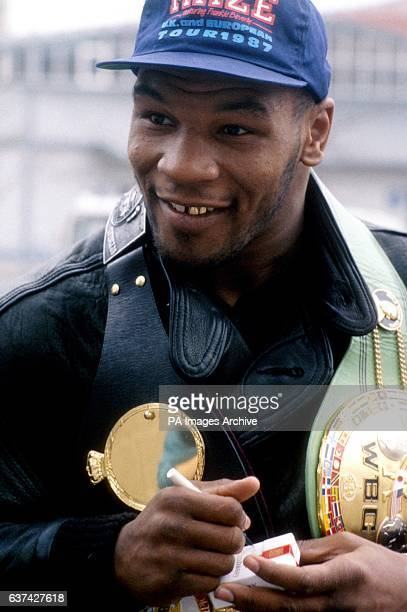 World Heavyweight Champion Mike Tyson signs an autograph on a cigarette packet