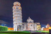 World heritage Pisa tower, baptistery and cathedral at night. Famous tourist attraction, symbol of Italy