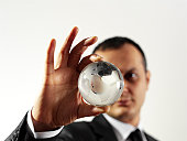 businessman holding glass globe