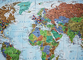 A paper world map hanging on a wall dotted with colorful pins marking destinations