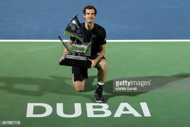 TOPSHOT World number one Andy Murray of Great Britain celebrates with the championship trophy after winning his ATP final tennis match against...