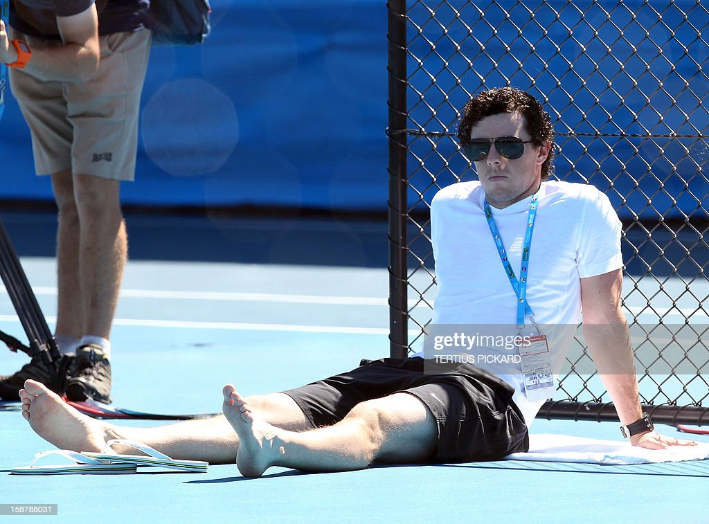 World number one golfer Rory McIlroy of Northern Ireland (R) watches girlfriend Caroline Wozniacki of Denmark during a training session in Brisbane on December 29, 2012, ahead of the upcoming Brisbane International tennis tournament. Top international men's and women's players are using the Brisbane International as a build-up to the Australian Open, which runs from January 14 to 27. AFP PHOTO/Tertius PICKARD USE