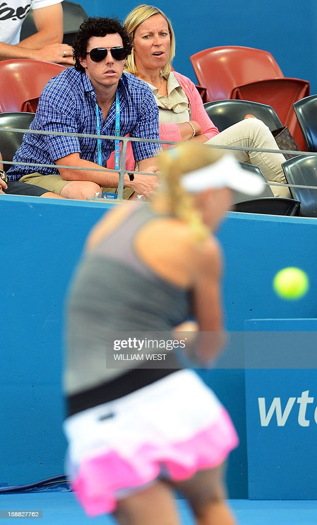World number one golfer Rory McIlroy of Northern Ireland (top L) watches girlfriend Caroline Wozniacki of Denmark (bottom) lose to Ksenia Pervak of Kazakhstan in the first round at the Brisbane International tennis tournament on December 31, 2012. AFP PHOTO/William WEST USE