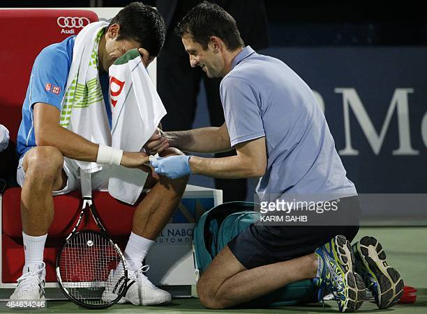 World number one Novak Djokovic of Serbia receives medical treatment after he fell during his semifinal tennis match against Tomas Berdych of the...