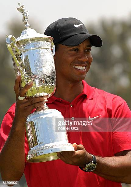World number one Tiger Woods of the US holds his trophy after defeating compatriot Rocco Mediate to win his third US Open title on the first hole of...
