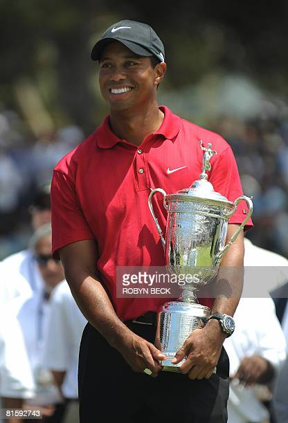 World number one Tiger Woods of the US holds the trophy after defeating compatriot Rocco Mediate in the sudden death playoff at the 108th US Open...