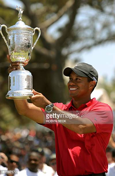 World number one Tiger Woods of the US shows off his trophy after defeating compatriot Rocco Mediate to win his third US Open title on the first hole...