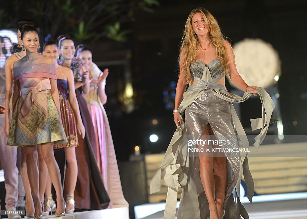 World number one woman's tennis player Victoria Azarenka of Belarus walks the cat walk during the Thai silk fashion show in Thailand's resort seaside town of Hua Hin on December 28, 2012. Azarenka will play an exhibition match with Li Na at the Hua Hin World Tennis Invitation on December 29. AFP PHOTO / PORNCHAI KITTIWONGSAKUL