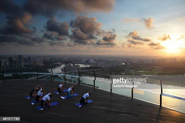 World number three tennis player Simona Halep of Romania takes part in a sunrise yoga session at SkyPark Observation Deck at Marina Bay Sands on July...